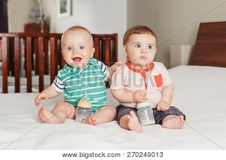 Group Portrait Of Two White Caucasian Cute Adorable Funny Baby Boys Sitting Together On Bed Socializ