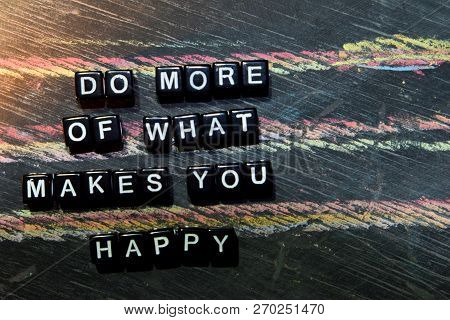 Do More Of What Makes You Happy On Wooden Blocks. Cross Processed Image With Blackboard Background.