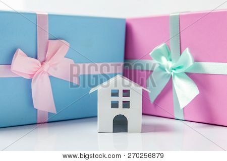 Miniature White Toy House And Gift Box Wrapped Pink Blue Paper Isolated On White Background. Mortgag