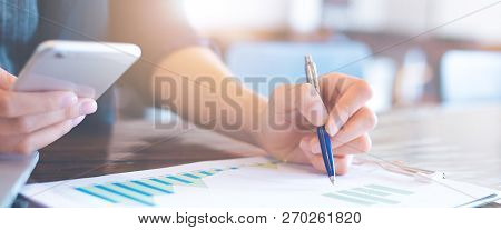Businessman Working On Analysis Charts And Graphs Showing Results.her Hand Holds The Pen And Points