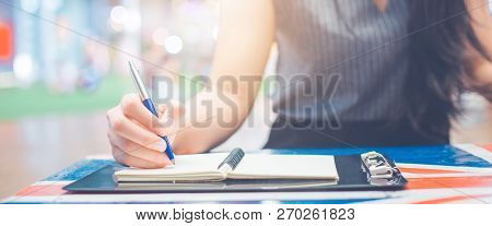 Woman Hand Writing On A Notepad With A Pen.