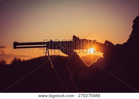 Calibers of hunting rifles. Rifle Hunter Silhouetted in Beautiful Sunset. Silhouette of the hunter. Pulled the trigger of the shotgun. Barrel of a gun poster