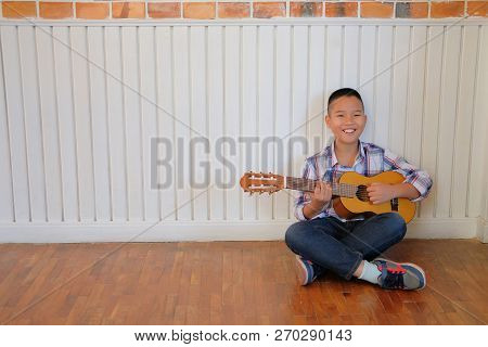 Asian Kid Boy Child Playing Guitar Ukulele. Children Leisure Activity