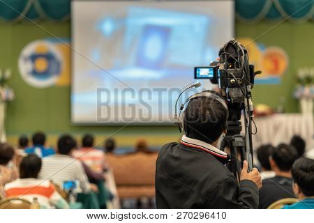 Rear Side Of Video Cameraman Taking Photograph To Asian Speaker With Casual Suit On The Stage Presen