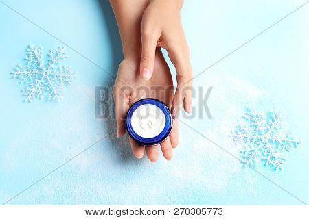 Woman Holding Jar Of Moisturizing Cream On Color Background, Top View. Winter Skin Care Cosmetic