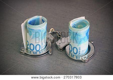 Roll Israeli Money Bills (banknotes) Of 200 Shekel In Handcuffs. Shekel Bills With Handcuffs. Handcu