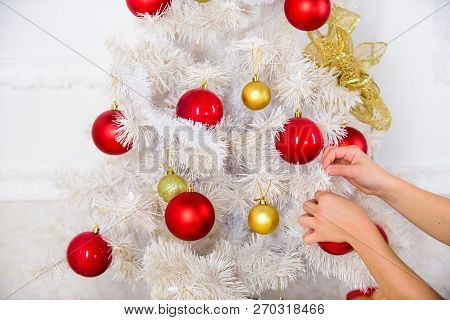 Hands Of Child Put Christmas Ornament Ball On Artificial White Tree. Christmas Decoration Concept. E