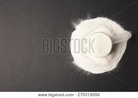 Pile Of Protein Powder, Scoop And Space For Text On Black Background, Top View. Preparing Shake