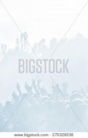 Crowd of spectators at a concert in light blue tonality. High key background with a people on an open playground at a concert. Abstract soft focus image with copy space poster