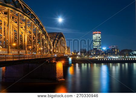 View Of The Hohenzollern Bridge, The Illuminated Skyscraper Cologne Triangle, The Long River Rhine (