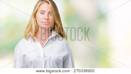 Beautiful young business woman over isolated background Relaxed with serious expression on face. Simple and natural looking at the camera.