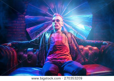 A crazy disco man is on the sofa. Party, disco. Colorful light.