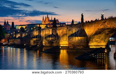 Sunset Over Illuminated Charles Bridge In Prague