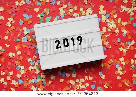 Year 2019 - Numbers On Lightbox Sign On Red Paper Background With Confetti - New Years Eve Party Cel