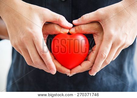 Red Heart Held By Male And Female's Both Hands, Represent Helping Hands, Help Each Other, Love, Part