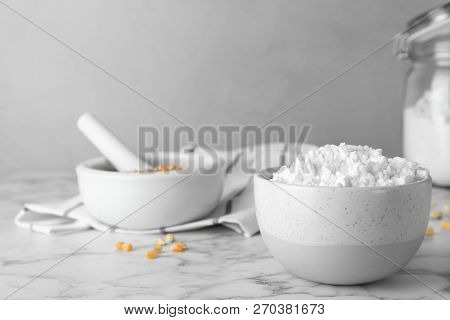 Bowl with corn starch on marble table. Space for text poster