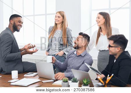 Multiracial Work Team Talking During Coffee Break At Meeting In Office