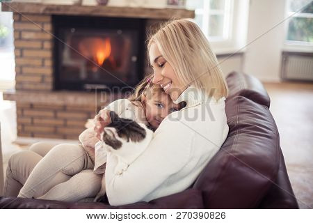 Mom And Little Cute Girl 3 Years Old Playing With A Cat. Happy Mother And Daughter, A Cat Sitting By