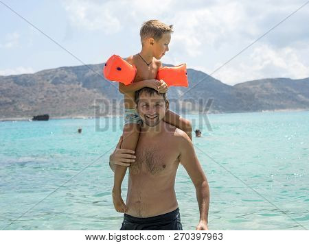 Happy Father Giving Shoulder Ride On His Shoulders At The Beach. Happy Smiling Boy On Shoulder Dad L