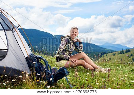 Beautiful Woman Tourist Hiking Mountain Trail, Sitting Near Tent And Backpack, Smiling To The Camera