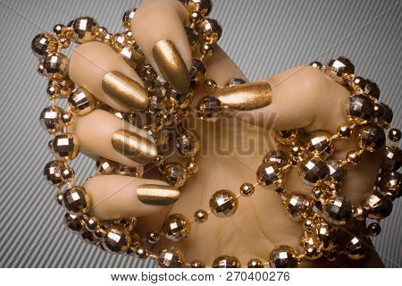 Female Hand With Bronze Nails Is Holding Bronze Pearl Jewelry On Gray Striped Background, Nail Care