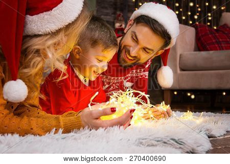 Family In Santa Hats With Child Kid Boy Playing With Light Christmas Garland In Warm Red Sweaters Ly