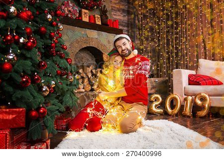 Romantic Couple In Love Woman Female Wife In Light Christmas Light Garland And Man Male Husband Hugg
