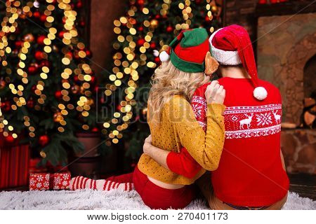 Couple In Love, Man Male Husband And Woman Female Wife In Santa Elf Hats And Warm Red Sweaters Huggi