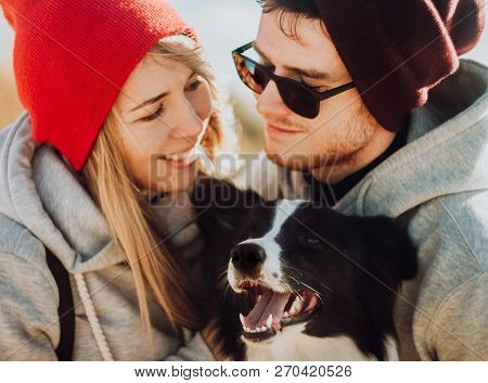 Smiling Couple Of Travelers In Cool Sunglasses Whit Cool Dog Of Setting Sun. Happy People Relax In N