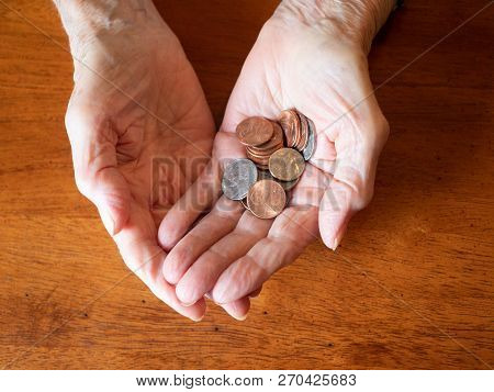 Close Up Of Elderly Woman's Hands Holding Coins