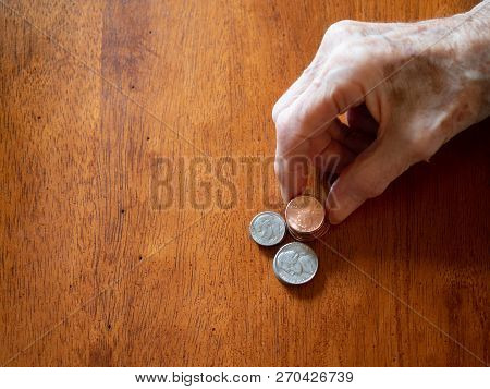 An Elderly Woman Stacking Pennies, Nickles And Dimes On A Wooden Table. Only Her Wrinkles Hands Are