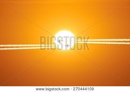 Sun And Airplane With Contrails On The Orange Sky.