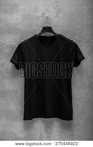 Front Side Of Male Black Cotton T-shirt On A Hanger And A Concrete Wall In The Background. T-shirt W