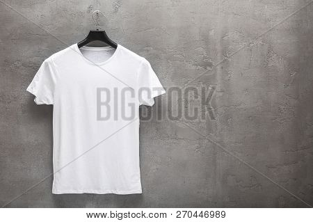 Front Side Of Male White Cotton T-shirt On A Hanger And A Concrete Wall In The Background. T-shirt W