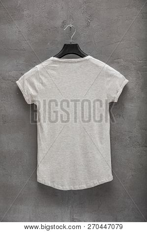 Back Side Of Female Grey Melange Cotton T-shirt On A Hanger And A Concrete Wall In The Background. T