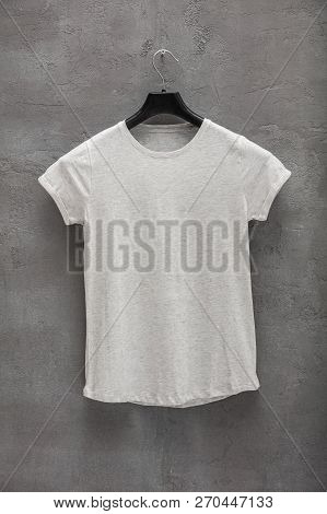 Front Side Of Female Grey Melange Cotton T-shirt On A Hanger And A Concrete Wall In The Background.