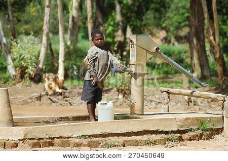 Mzuzu, Malawi - December 12, 2008: Child Near A Water Pump In A Small Village