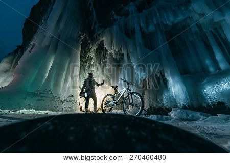 Surreal Landscape With Woman Exploring Mysterious Ice Grotto Cave. Outdoor Adventure Bike. Girl Expl