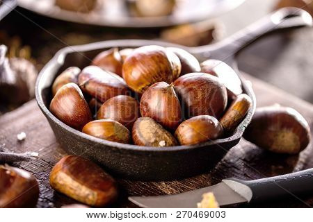 Roasted Chestnuts Served In A Special Perforated Chestnut Pan On An Old Wooden Table.
