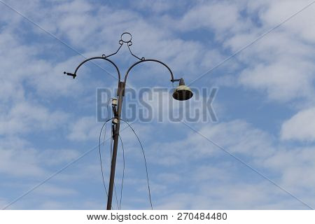 Old Lamppost On The Background Of Cloudy Sky.