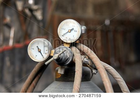 Two Pressure Gauges To Check The Pressure In Oxygen Cylinders, Against The Blurred Wall Of The Works