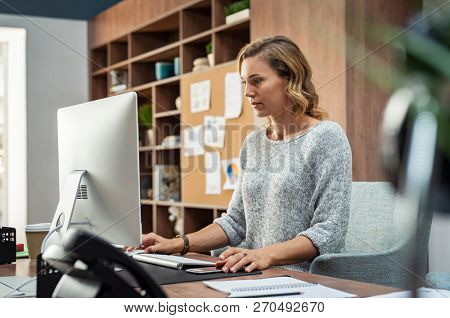 Mature businesswoman working on desktop computer at modern office. Concentrated freelancer finishing project sitting in coworking space using desktop computer. Creative business woman sending email.