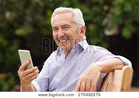 Senior man using smartphone while sitting on bench at park. Portrait of handsome old man using smart phone outdoor. Happy smiling grandfather holding mobile phone and looking at camera.
