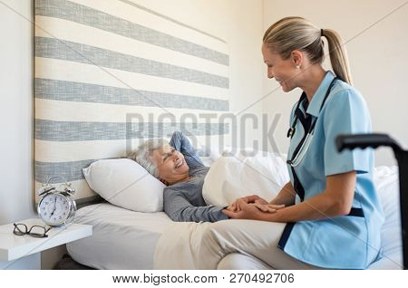 Friendly nurse with senior woman at home. Smiling nurse talking with her patient while getting her out of bed. Disabled woman getting regular health checkup done at home with doctor.