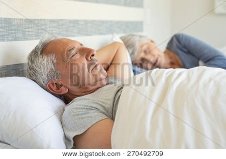 Senior man and woman sleeping on bed. Mature couple resting with eyes closed during the morning. Old husband and wife sleeping together in their bed with peace.