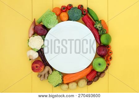 Health food for vegans with fresh fruit, vegetables, spices and herbs surrounding a porcelain dinner plate on yellow wood background. High in antioxidants, vitamins, dietary fibre and omega 3.