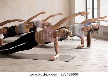 Group Of Women Practicing Yoga Lesson, Side Plank Exercise
