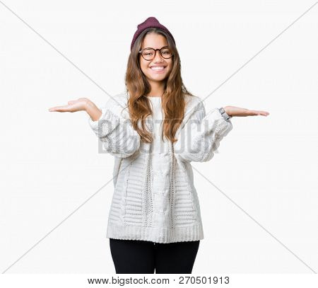 Young beautiful brunette hipster woman wearing glasses and winter hat over isolated background Smiling showing both hands open palms, presenting and advertising comparison and balance