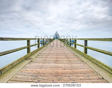 Perspective View Of A Wooden Pier On Moody Ocean. Vintage Wooden Pier At The Beach