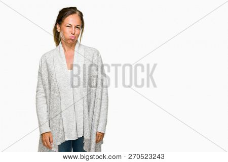 Beautiful middle age adult woman wearing winter sweater over isolated background puffing cheeks with funny face. Mouth inflated with air, crazy expression.